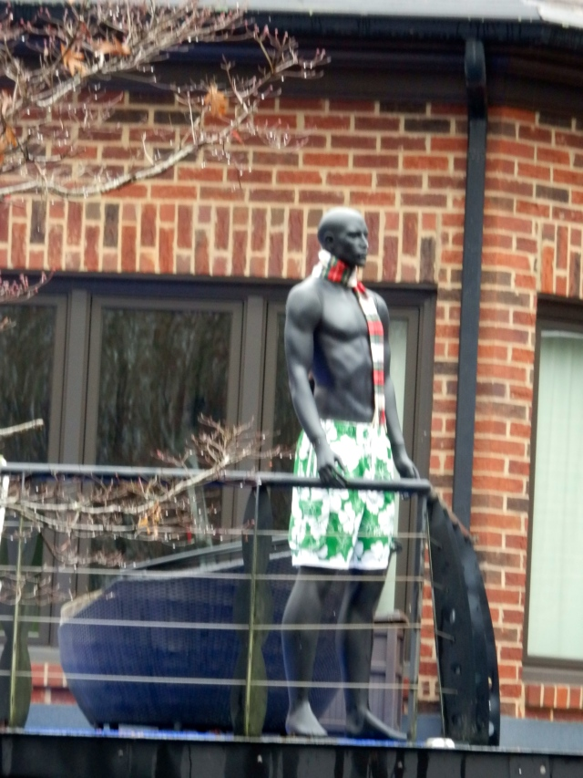 Statue off upper balcony.  Swim trunks and winter scarf.
